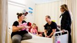 A long shot of a woman sitting on a hospital bed holding a baby while a woman stands and a man and a young child sit watching